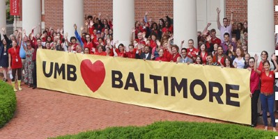UMB students gathered around a banner that reads 'UMB loves Baltimore'