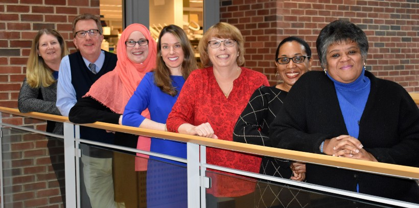 The staff of Academic Affairs posing by a loft railing