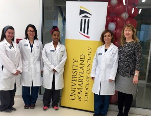 Sheryl Syme and three dental hygiene students in white coats standing by a banner for the University of Maryland School of Dentistry