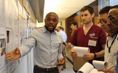 Incoming D1 student Chimdi Ego-Osuala presents his research to the judges panel during the poster competition held July 28.