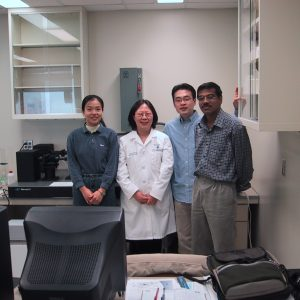 Dr. Lowe in a lab coat with lab members