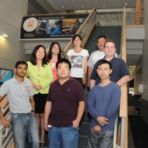 Lab members posing together on a staircase