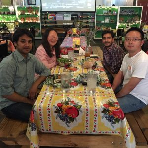 Lab members having a meal together at a long table in a restaurant