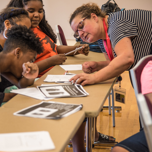 Ann Felauer, MSN, RN, CPNP-AC/PC, clinical instructor at the University of Maryland School of Nursing, engages eighth-grade CURE Scholars during the mathematical portion of a forensics lab.